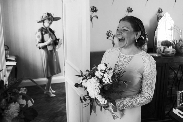 bridesmaid laughing with mother of bride