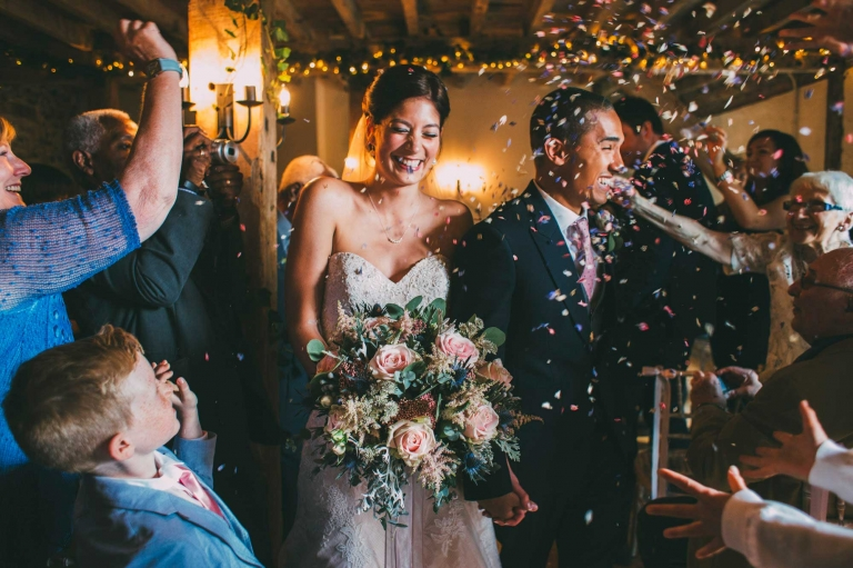 bride and groom laugh during confetti throwing